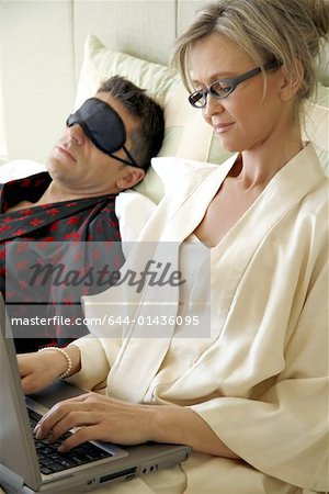 Mature couple relaxing in bed Stock Photo - Premium Royalty-Free, Image code: 644-01436095