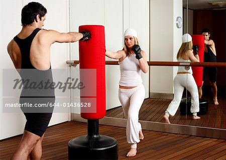 Young man and woman hitting the punching bag Stock Photo - Premium Royalty-Free, Image code: 644-01436528