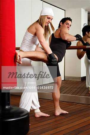 Young man and woman practicing with a punching bag Stock Photo - Premium Royalty-Free, Image code: 644-01436972