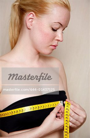 Woman measuring her chest Stock Photo - Premium Royalty-Free, Image code: 644-01437125