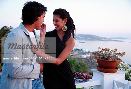 Couple eating grapes on balcony Stock Photo - Premium Royalty-Free, Image code: 644-01437303