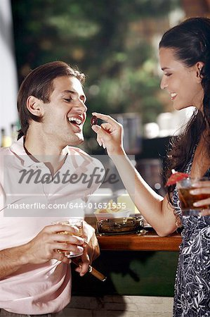 Woman feeding man in a bar Stock Photo - Premium Royalty-Free, Image code: 644-01631535