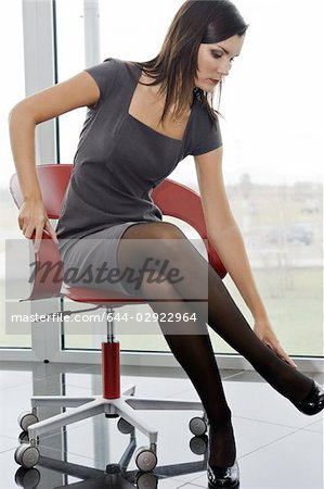 Professional woman sitting on office chair adjusting her heel Stock Photo - Premium Royalty-Free, Image code: 644-02922964