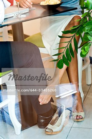 Young woman's bare foot touching young man's leg under table Stock Photo - Premium Royalty-Free, Image code: 644-03405260