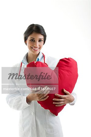 Doctor holding heart pillow Stock Photo - Premium Royalty-Free, Image code: 644-03659607