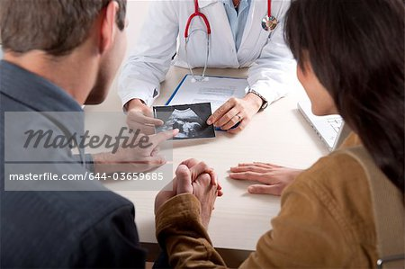 Doctor with ultrasound and couple Stock Photo - Premium Royalty-Free, Image code: 644-03659685