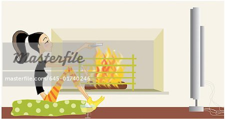 Woman sitting in front of fireplace watching TV Stock Photo - Premium Royalty-Free, Image code: 645-01740246