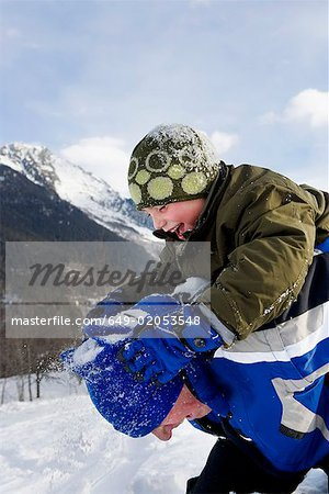 Boy playing with grandfather in snow Stock Photo - Premium Royalty-Free, Image code: 649-02053548