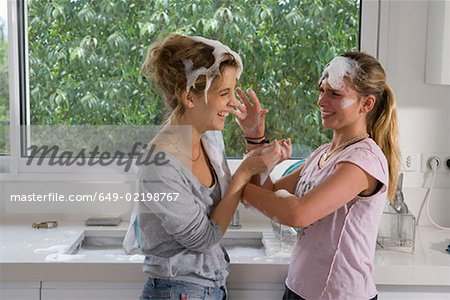 Sisters having soap bubble fight at sink Stock Photo - Premium Royalty-Free, Image code: 649-02198767