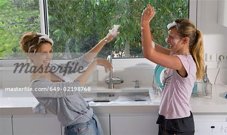 Sisters having bubble soap fight at sink Stock Photo - Premium Royalty-Free, Image code: 649-02198768