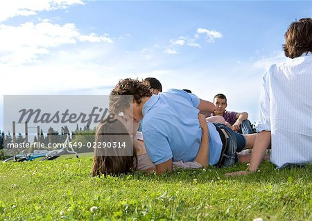 Teen lovers kissing in front of friends Stock Photo - Premium Royalty-Free, Image code: 649-02290314