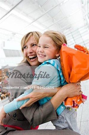 Woman holding flowers embracing girl Stock Photo - Premium Royalty-Free, Image code: 649-02423656