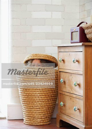 Child hiding in laundry basket Stock Photo - Premium Royalty-Free, Image code: 649-02424009