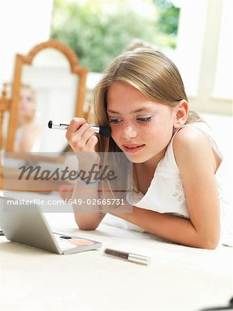Girl putting on make-up Stock Photo - Premium Royalty-Free, Image code: 649-02665731