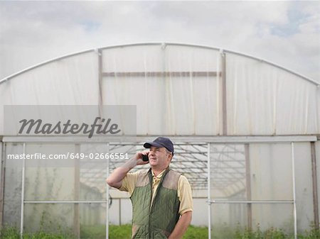 Farmer On Mobile Outside Polytunnel Stock Photo - Premium Royalty-Free, Image code: 649-02666551
