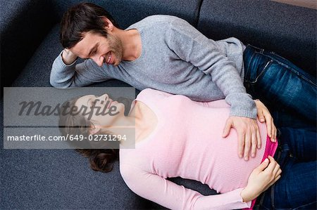 Pregnant woman and man laying on couch Stock Photo - Premium Royalty-Free, Image code: 649-02731294