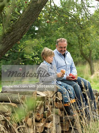 Man and boy with apples,sitting on logs Stock Photo - Premium Royalty-Free, Image code: 649-03008695