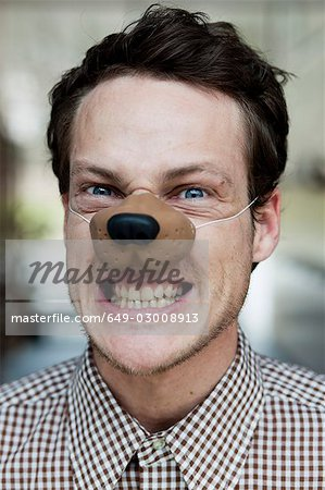 man with toy dog nose snarling Stock Photo - Premium Royalty-Free, Image code: 649-03008913