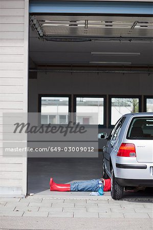 young girl lying under car cleaning Stock Photo - Premium Royalty-Free, Image code: 649-03009012