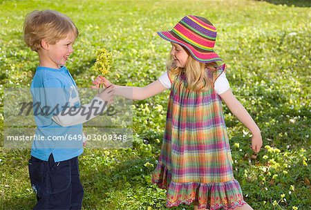 girl giving spring flower bouquet to boy Stock Photo - Premium Royalty-Free, Image code: 649-03009348