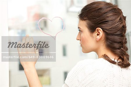 Woman looking sadly at a painted heart. Stock Photo - Premium Royalty-Free, Image code: 649-03009686