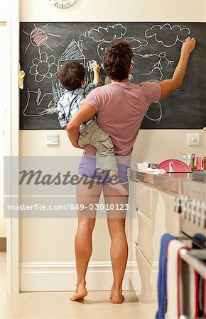 father and son drawing on chalkboard Stock Photo - Premium Royalty-Free, Image code: 649-03010123