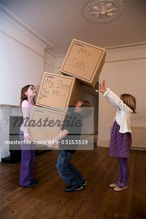 Three children moving a stack of boxes Stock Photo - Premium Royalty-Free, Image code: 649-03153519