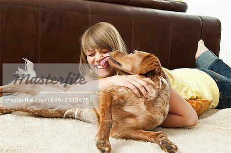 Pet dog licking a young woman's face Stock Photo - Premium Royalty