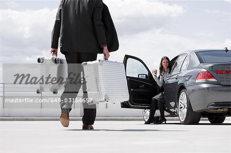 man carrying cases woman waiting in car Stock Photo - Premium Royalty-Free, Image code: 649-03154657