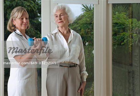 Nurse helping woman with exercises Stock Photo - Premium Royalty-Free, Image code: 649-03292161