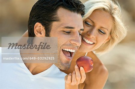 A female feeding a latin man an apple. Stock Photo - Premium Royalty-Free, Image code: 649-03292925