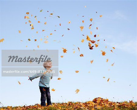 boy throwing autumn leaves into the air Stock Photo - Premium Royalty-Free, Image code: 649-03362915