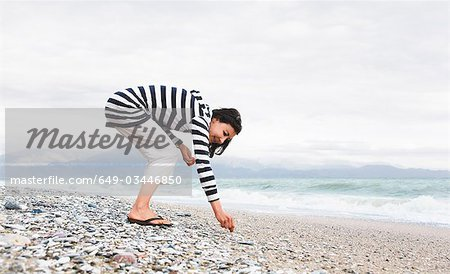 Woman picking shells on a beach Stock Photo - Premium Royalty-Free, Image code: 649-03446850