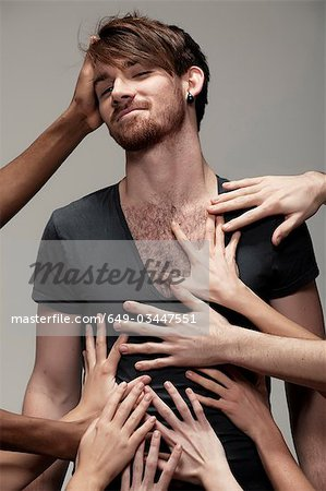 Young man being touched by hands Stock Photo - Premium Royalty-Free, Image code: 649-03447551