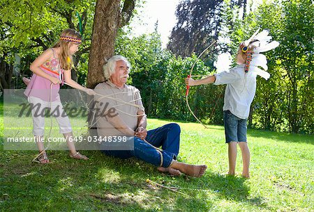 Grandchildren got their grandfather tied Stock Photo - Premium Royalty-Free, Image code: 649-03448398