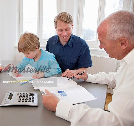 Advisor discussing papers with a father Stock Photo - Premium Royalty-Free, Image code: 649-03465856