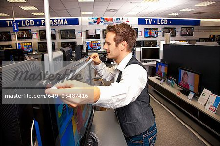 Measuring out a large-sized flatscreen Stock Photo - Premium Royalty-Free, Image code: 649-03487416
