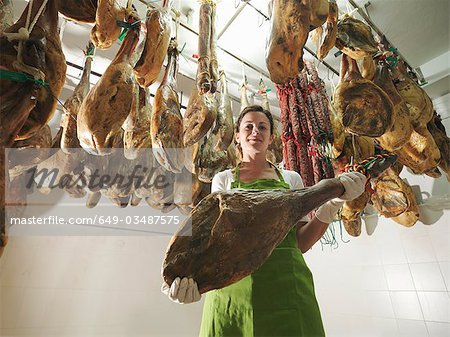 Woman holding a ham leg Stock Photo - Premium Royalty-Free, Image code: 649-03487575