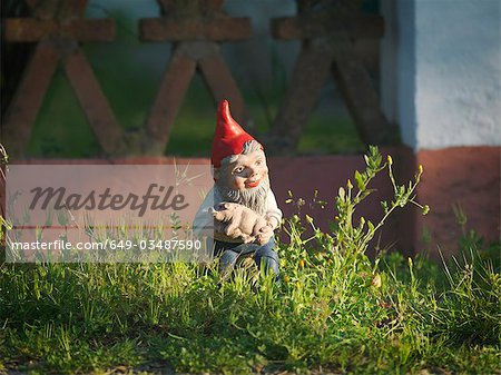 Garden gnome holding piglet Stock Photo - Premium Royalty-Free, Image code: 649-03487590