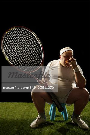 Tennis player with large racquet sitting Stock Photo - Premium Royalty-Free, Image code: 649-03511270