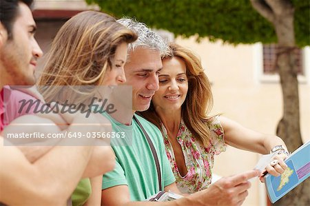 Two couples looking at postcard Stock Photo - Premium Royalty-Free, Image code: 649-03566363