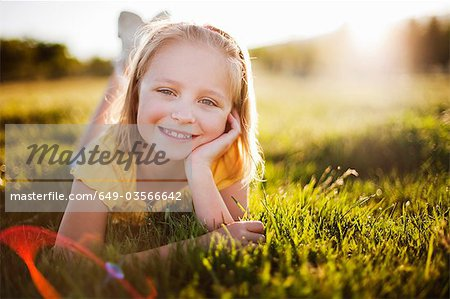 Young girl in grass smiling Stock Photo - Premium Royalty-Free, Image code: 649-03566642