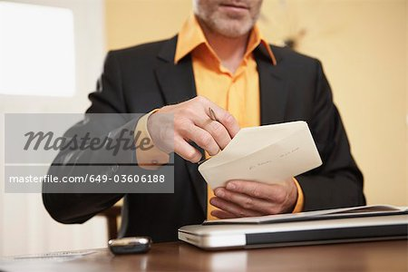 Man opening letter Stock Photo - Premium Royalty-Free, Image code: 649-03606188