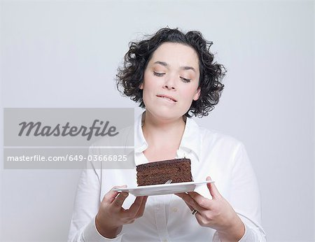 woman looking at plate of cake Stock Photo - Premium Royalty-Free, Image code: 649-03666825