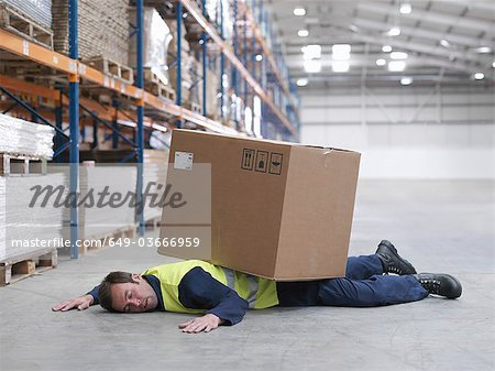 Worker Flattened By Box In Warehouse Stock Photo - Premium Royalty-Free, Image code: 649-03666959