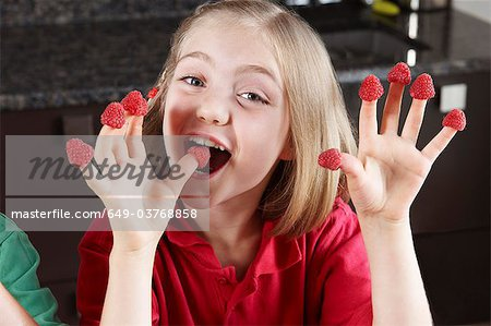 Girl with raspberries on fingers Stock Photo - Premium Royalty-Free, Image code: 649-03768858