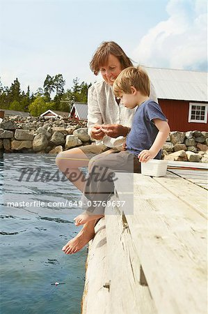 Woman with grandson fishing from jetty Stock Photo - Premium Royalty-Free, Image code: 649-03769637