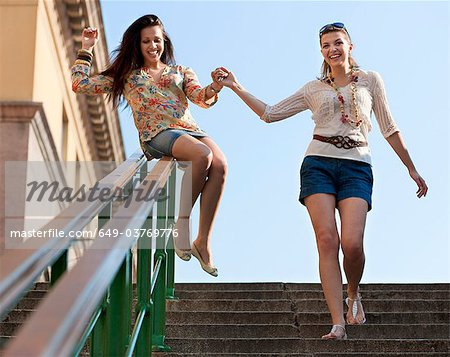 Young women sliding down railing Stock Photo - Premium Royalty-Free, Image code: 649-03769776