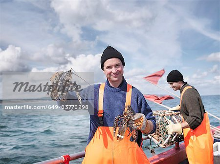 Fishermen on boat holding lobsters Stock Photo - Premium Royalty-Free, Image code: 649-03770298