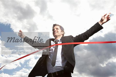 Businessman crossing finish line Stock Photo - Premium Royalty-Free, Image code: 649-03770636